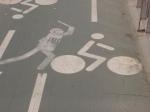Un policía y un ciclista dibujados en el piso de una calle.